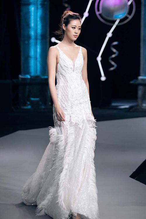 Sở hữu kỹ năng catwalk điêu luyện, vóc dáng đẹp, nàng Hậu dễ dàng chinh phục thiết kế váy cưới đuôi cá. Mẫu đầm được xẻ ngực chữ V, đính họa tiết ren nổi, điểm thêm lông vũ nơi chân váy - xu hướng được nhiều nhà thiết kế dự đoán là hot trend của năm 2020. Ảnh: Kiếng Cận