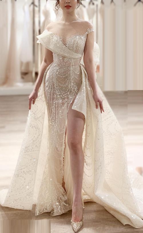 Điểm đặc biệt hơn cả trong thiết kế là khi tháo lớp tùng xòe bên ngoài và điều chỉnh phần vai váy, cô dâu đã nhanh chóng có một phong cách khác: gợi cảm, quyến rũ với váy đuôi cá xẻ đùi cao.