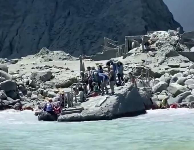 Nhóm du khách được đưa đi lánh nạn khi núi lửa phun trào trên đảo Whakaari, New Zealand, chiều 9/12. Ảnh: Twitter.