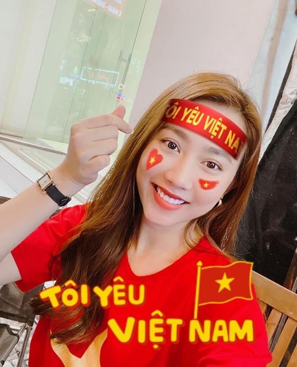 Diễn viên Huỳnh Hồng Loan trong sắc áo đỏ, rạng rỡ chờ theo dõi trận cầu kịch tính.