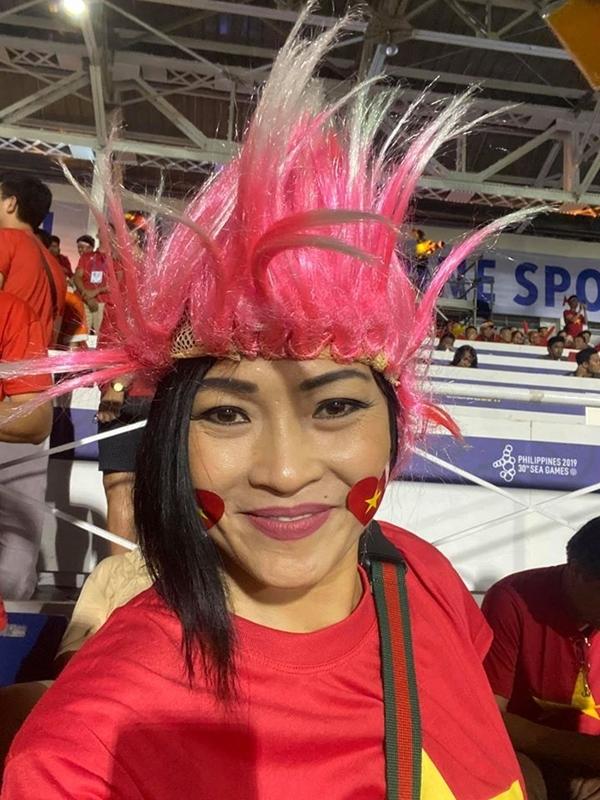 Phương Thanh là số ít sao Việt được thưởng thức trận cầu trực tiếp. Nữ ca sĩ trong trang phục vận động viên, đội tóc đỏ, dán quốc kỳ lên má.