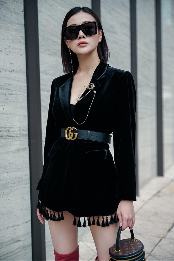 Bộ trang phục tối màu trở nên cuốn hút hơn với khuyên tai phá cách, có thể cài lên áo và phần đính tua rua bắt mắt.