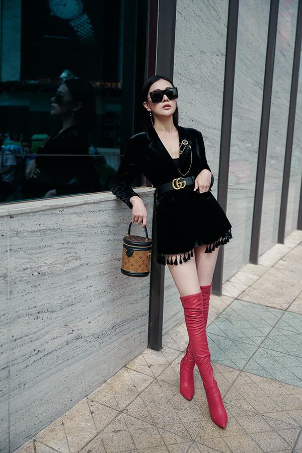 Với vest nhung màu đen, cô phối cùng kết hợp với dây lưng cùng tông của Gucci, boot cao cổ màu đen và kính râm to bản.