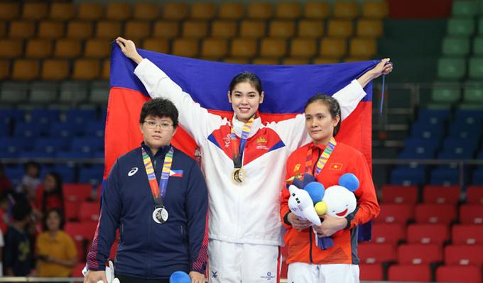 Bóng hồng làng võ Campuchia xinh tươi rạng rỡ trên bục huy chương. Ở hạng cân này, võ sĩ Lâm Thị Thanh Hà của Việt Nam giành HC đồng.
