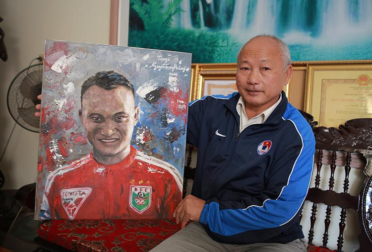Ông Hường bên bức tranh một cổ động viên đã vẽ tặng Trọng Hoàng nhiều năm trước. Ảnh: Nguyễn Hải.