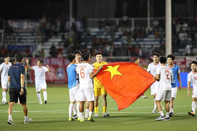 Thủ môn Bùi Tiến Dũng và các đồng đội cầm cờ tổ quốc chuẩn bị cho màn chạy diễu hành quanh sân. Ở trận đấu vòng bảng thắngIndonesia 2-1, Bùi Tiến Dũng bắt chính và mắc lỗi trong bàn thua duy nhất.