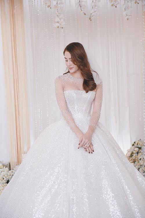 NTK đã tối giản toàn bộ chi tiết trên thân váy theo xu hướng thời trang cưới hiện đại. Dải pha lê được nhấn nhá ở cổ và cánh tay tạo điểm nhấn cho toàn bộ trang phục, tôn vinh nét đẹp sang trọng vốn có của cô dâu Lê Hà.