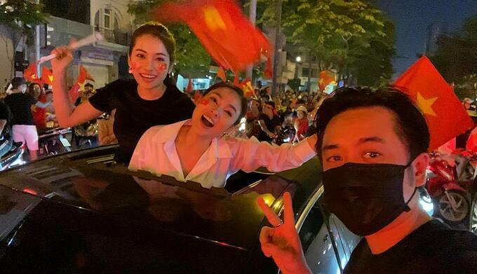 Vợ chồng Dương Khắc Linh cùng bạn xuống phố ăn mừngcùng rừng người rợp cờ đỏ sao vàng.