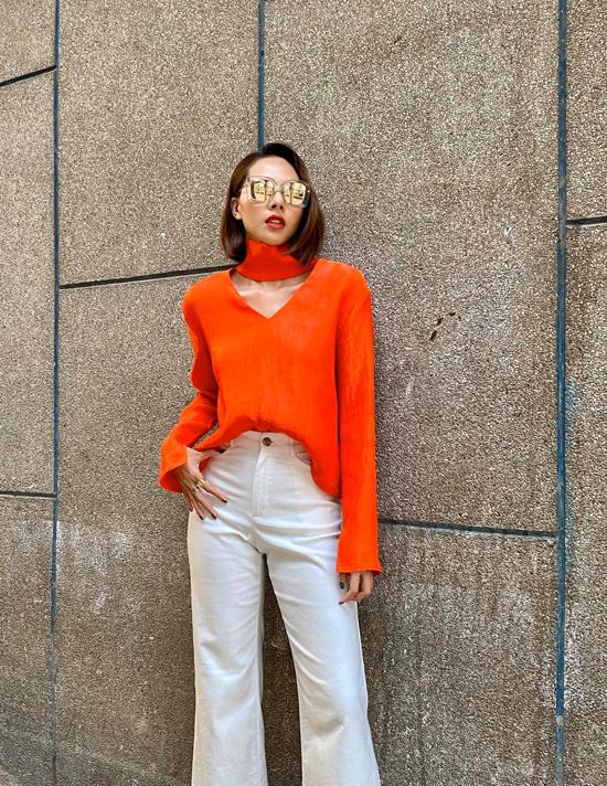 Minh Triệu với kiểu áo cổ lọ có thiết kế độc đáo do chính cô thiết kế. Siêu mẫu chia sẻ, ở mùa này tông cam có sức hút mạnh mẽ đối với cô.