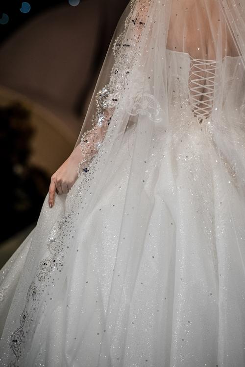 Bộ cánh có phần dây đan mặt lưng, giúp siết vòng eo con kiến của cô dâu. Mẫu đầm được kết hợp với voan cưới họa tiết hoàng gia, điểm thêm sequin lấp lánh.