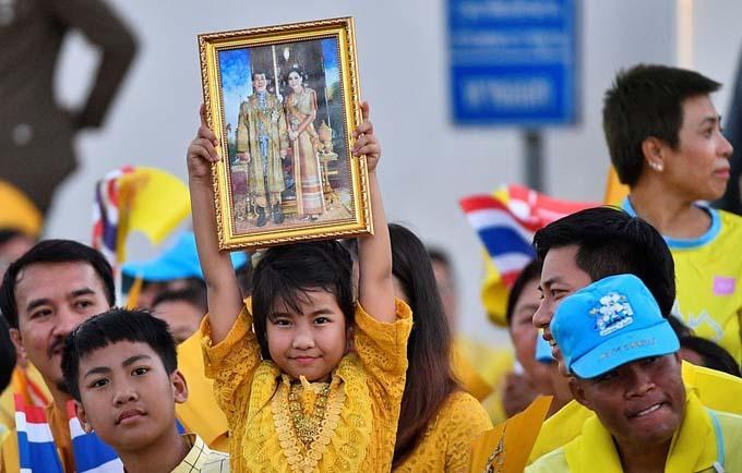 Một bé gái giơ cao khung ảnh có hình Quốc vương Rama X và Hoàng hậu Suthida để tỏ lòng tôn kính.