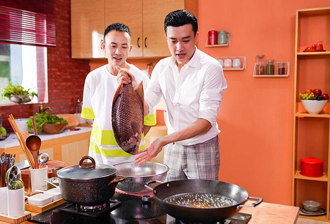 Nam diễn viên làm món cá tai tượng chiên xù. Anh phải rất cẩn thận khi đặt con cá vào chảo dầu đang sôi. Anh Vũ nhận vai phụ bếp, giúp nhặt rau, chuẩn bị nguyên liệu cho Quốc Trường đứng nấu.