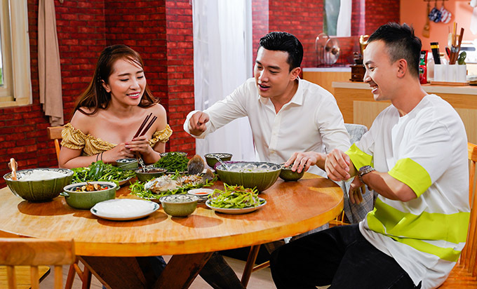 Bộ ba diễn viên phim Về nhà đi con quây quần bên bàn ăn có các món như đọt nhãn lồng luộc, ốc xào sả, cá tai tượng chiên xù.