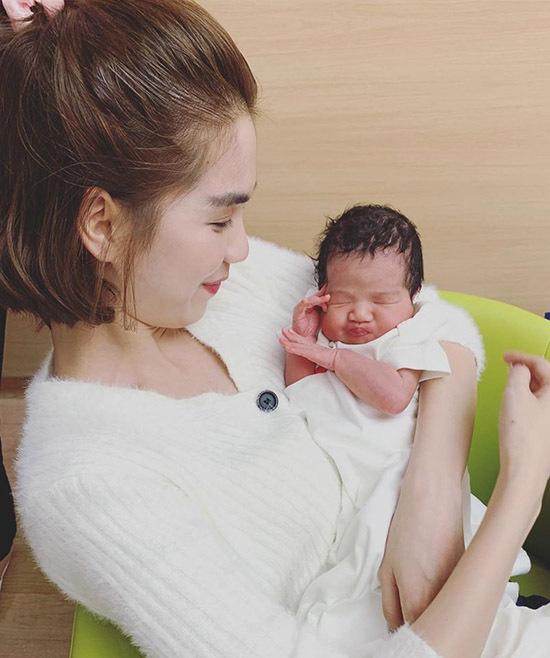Nữ hoàng nội y âu yếm bế cháu cưng. Cô bất ngờ vì tóc em bé mới sinh rất dày.