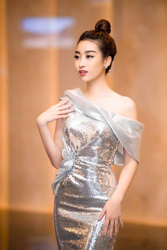Hoa hậu Đỗ Mỹ Linh quyến rũ với váy bất đối xứng phối hợp vải ánh kim bạc cùng voan lụa bóng bẩy.
