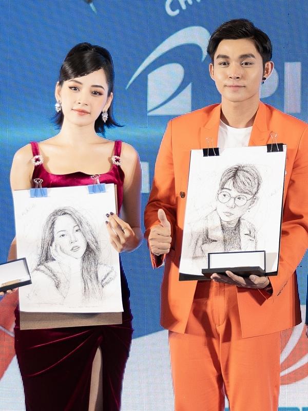 Hai nghệ sĩ bất ngờ trước món quà là bức tranh chân dung được ban tổ chức dành tặng.
