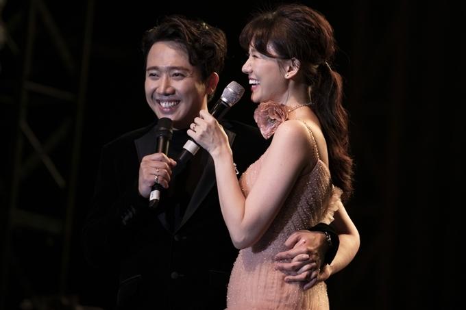 Trấn Thành tình tứ ôm eo vợ. Trước khi nhường lại sân khấu cho Hari Won hát một mình, anh không quên nhờ vả khán giả: Mọi người ủng hộ Trấn Thành ra sao thì cũng cổ vũ vợ em như vậy nhé.
