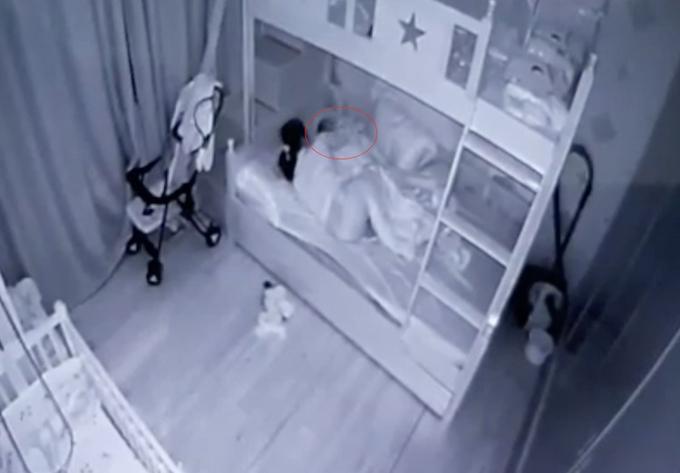 Bà Doan lúc đang ấnđầu nạn nhân (vòng tròn khoanh đỏ) xuống giường. Ảnh: Cắt từ video.