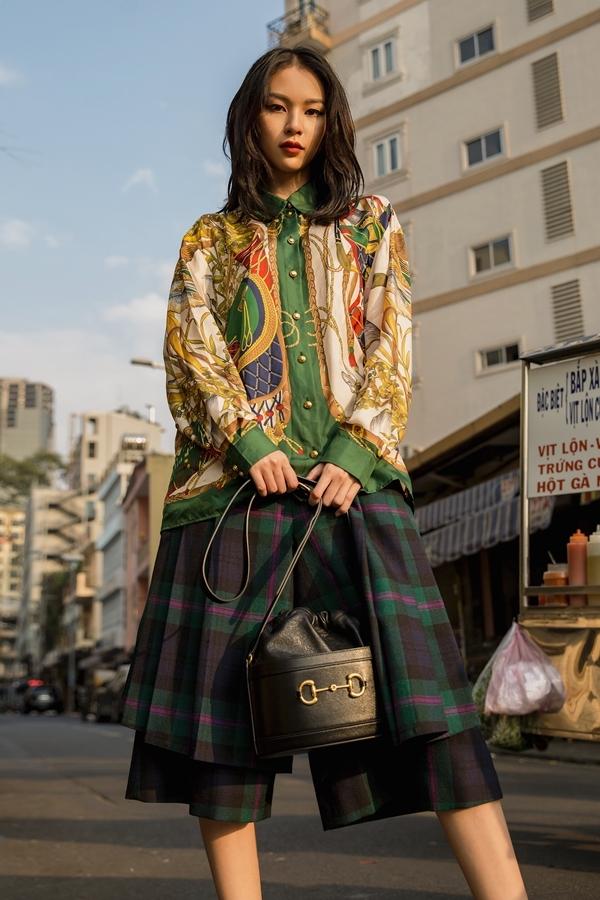 Phí Phương Anh nữ tính nhưng không kém phần năng động khi mix áo sơ mi họa tiết với quần váy kẻ ô.