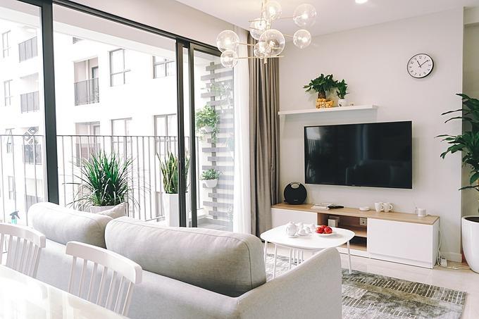 Phòng khách ngăn cách với ban công bằng hệ cửa kính, giúp lấy trọn ánh sáng tự nhiên.