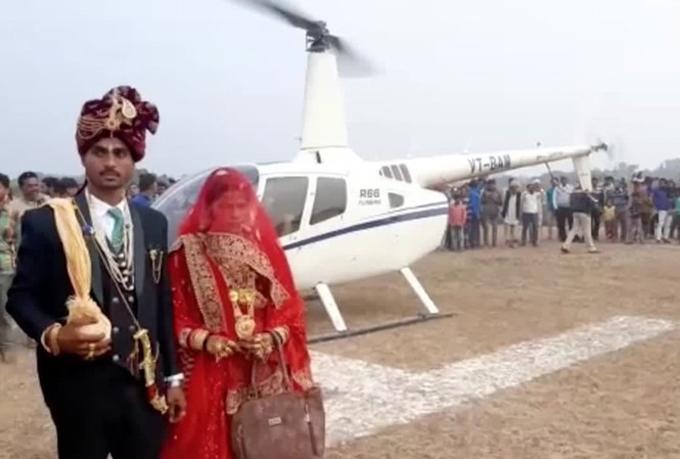 Cô dâu, chú rể bước ra khỏi trực thăng trước sự chứng kiến của đông đảo bạn bè, hàng xóm của gia đình chú rể.