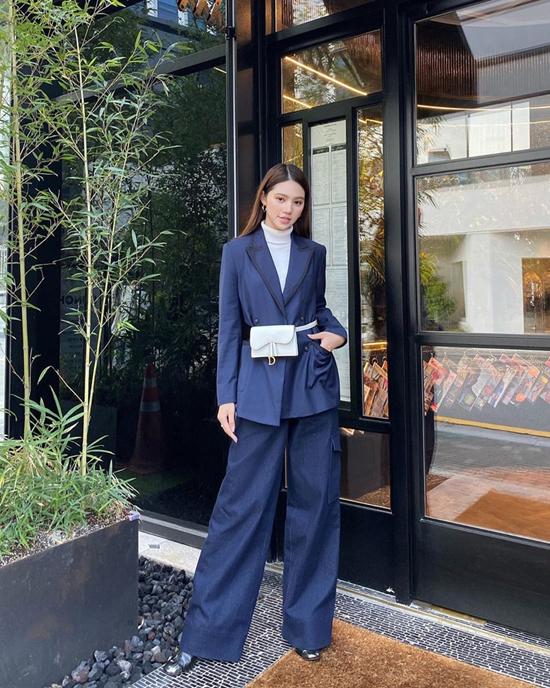 Jolie Nguyễn mix-match trang phục hài hòa tông xanh với blazer, quần denim, áo cao cổ và túi đeo hông tông trắng của Dior.