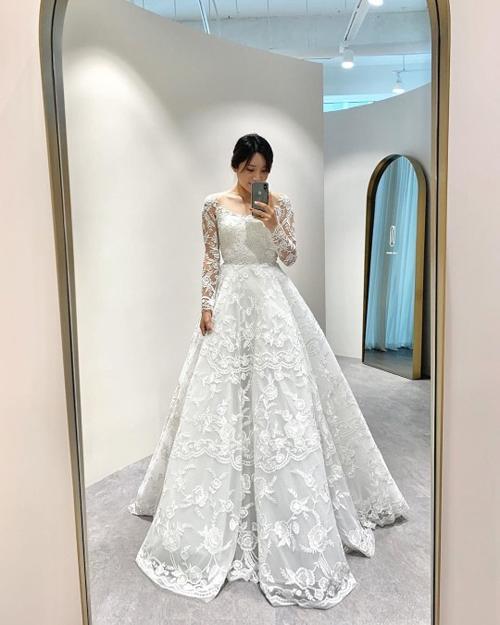 Trước dịp hỷ sự, người đẹp cũng tiết lộ những ảnh khi thử váy cưới. Mẫu đầm đầu tiên mà người đẹp mặc có họa tiết ren hoa hồng, cổ chữ U khoe xương quai xanh, phom dáng xòe.