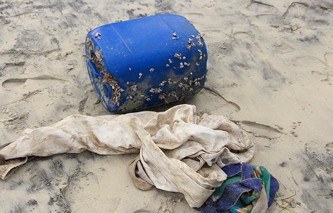 Can nhựa chứa heroin và áo quần dạt vào bờ biển do ông Lộc nhặt được. Ảnh: Võ Thạnh