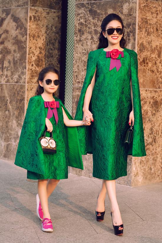 Váy liền thân trang trí thêm áo cape cho cả mẹ và bé được thiết kế trên chất liệu vải gấm sang trọng.