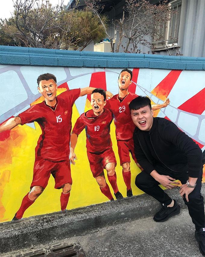 Quang Hải cũng thích thú chụp ảnh cùng tấm bích họa anh và đồng đội ăn mừng tại giảiAFF Cup 2018. Ảnh: Quang Hải.