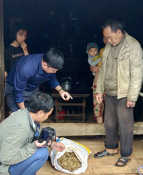 Ông Phù (trái) cùng nhà chức trách kiểm tra tiền cổ. Ảnh: Hùng Lê