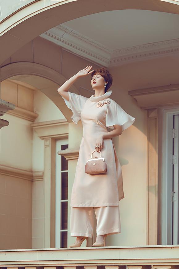 Khi diện áo dài, cô khéo léo kết hợp với giày và túi xách ton sur ton để tạo nên một tổng thể hoà hợp với màu sắc trung tính.