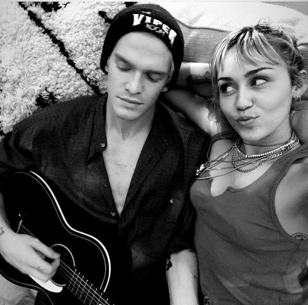 Miley nhìn yêu bồ trẻ khi anh gẩy đàn guitar.
