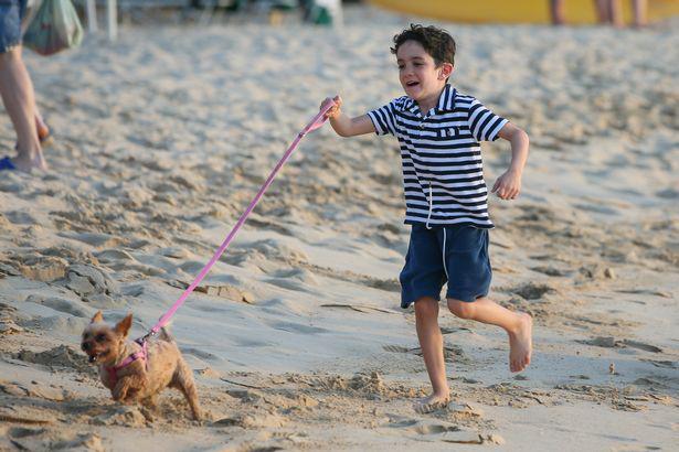 Cậu bé Eric tung tăng chơi đùa với cún trên bãi biển.