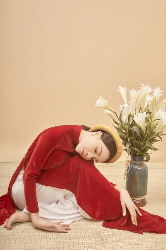 Diện áo dài nhung đỏ tươi, Trà Ngọc Hằng tạo dáng uyển chuyển bên hoa loa kèn.