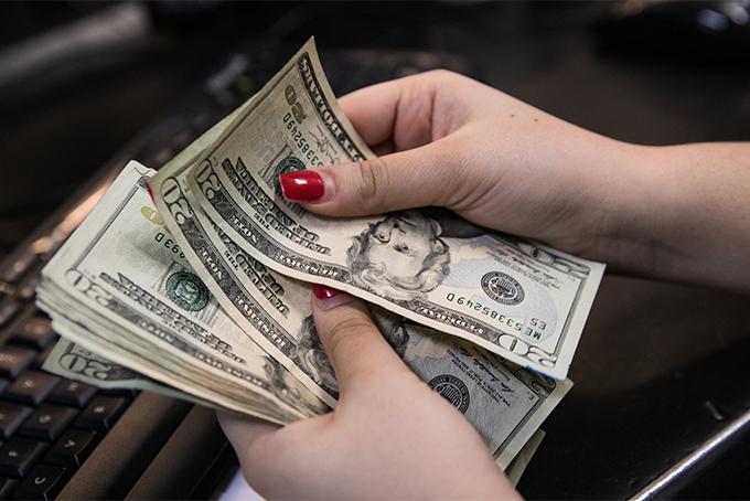 Theo các chuyên gia tài chínhnên để dành tiền thưởng cuối năm để trả nợ, lập quỹ khẩn cấp. Ảnh: NYT.