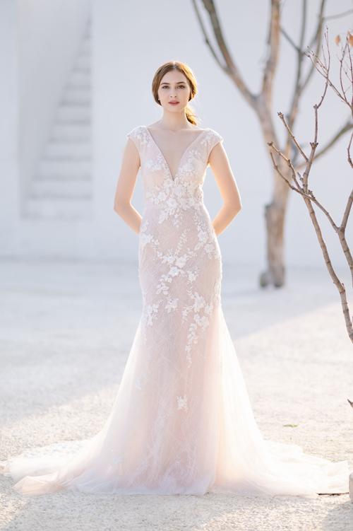 Mẫu đầm ren có cổ chữ V xẻ ngực sâu, phần vai áo cách điệu giúp cô dâu khoe nét đẹp nơi xương quai xanh.