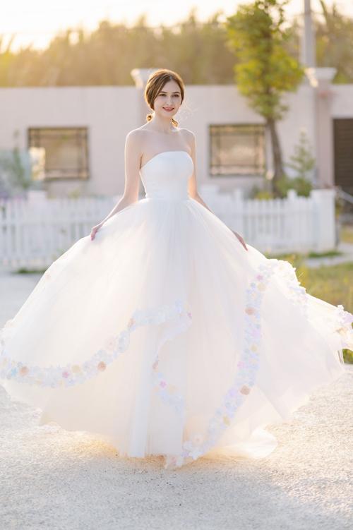 Bộ cánh cúp ngực có điểm nhấn là viền chân váy điểm họa tiết hoa, phản ánh tính cách trẻ trung, năng động của người diện.