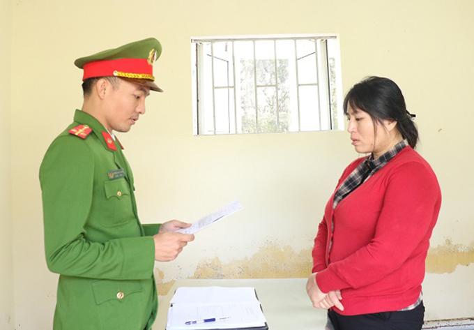 Nghi can Hoa (bên phải) nghe cảnh sát đọc lệnh bắt. Ảnh: C.A
