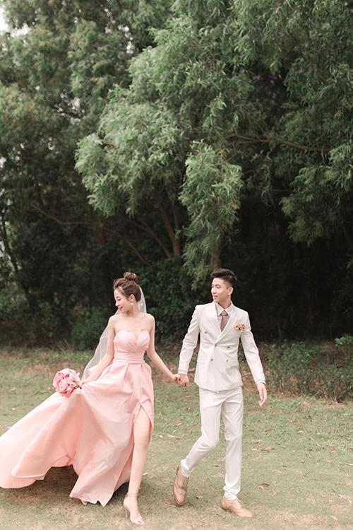 Concept ảnh cưới của uyên ương mang phong cách Hàn Quốc nhẹ nhàng, lãng mạn. Chú rể Văn Đức diện bộ suit trắng kem còn cô dâu của anh diện váy cúp ngực cổ tim, sắc hồng pastel. Thân váy có thiết kế xẻ tà, tôn đôi chân thon, nước da trắng ngần của tân nương.