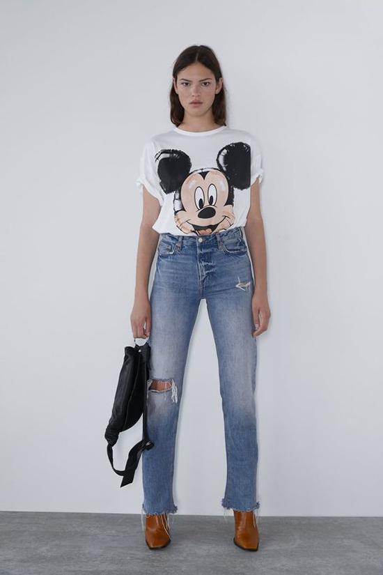 Cách đơn giản nhất để lên đồ đúng xu hướng thời trang 2020 là áo Mickey đi kèm quần jeans xanh cổ điển.