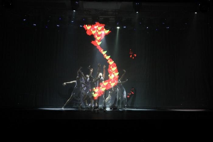 Phần trình diễn của anh được hỗ trợ bởi nhóm múa. Sân khấu được dàn dựng công phu, ứng dụng công nghệ 3D mapping để kể câu chuyện phát triển ngân hàng.