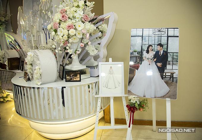 Bản vẽ phác thảo váy cưới chính của Ngọc Hà được đặt cạnh ảnh cưới của cặp vợ chồng.