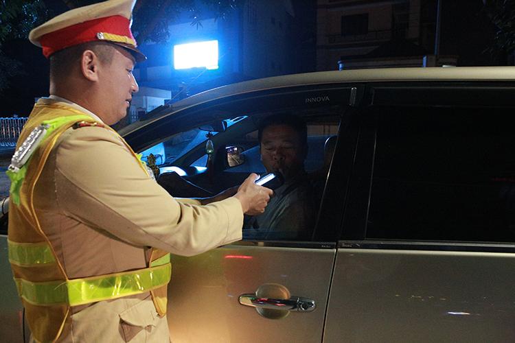 Cảnh sát kiểm tra nồng độ cồn một tài xế, song không phát hiện vi phạm. Ảnh: Anh Thư.