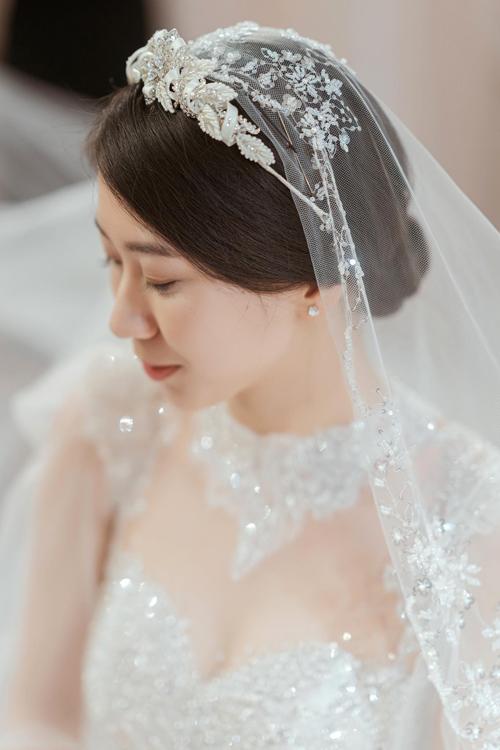 Phụ kiện cũng là yếu tố quan trọng giúp cô dâu hoàn thiện vẻ đẹp lộng lẫy. Vương miện hình hoa được chế tác cầu kỳ, khảm đá mang đúng tinh thần của xu hướngbaroque và rococo cổ điển, hài hòa với họa tiết thêu kết trên váy.