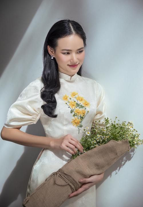 Dài dài tay bồng phảng phất phong cách cổ điển được trang trí hoa cục thêu tinh tế. Chất liệu vải gấm hoa cúc càng tăng thêm nét cuốn hút cho người mặc.