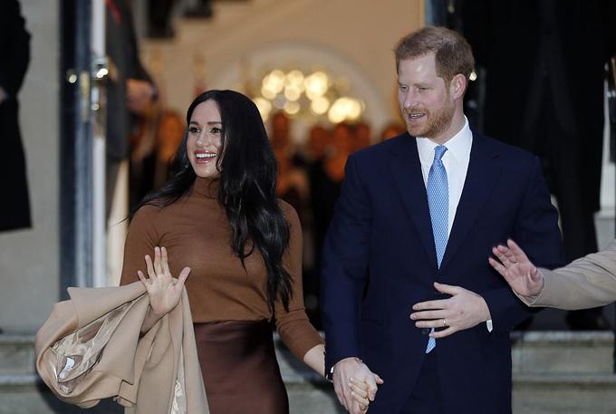 Nữ công tước xứ Sussex dùng một tay vẫy chào người hâm mộ trong khi tay kia vẫn nắm chặt chồng.