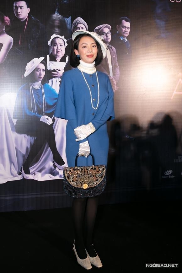 Thu Trang xuất hiện trong hình ảnh quý cô cổ điển với áo cổ lọ và váy dài cùng chuỗi hạt lớn.