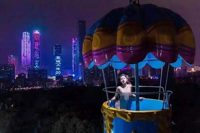 Mẫu nữ Zhang (20 tuổi) khỏa thân ở đu quay trên cao tại công viên thành phố Nam Ninh tối 31/12. Ảnh: WeChat.