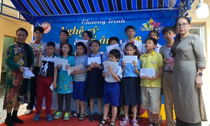 Nghệ sĩ Kim Xuân trao quà cho các cháu nhỏ.